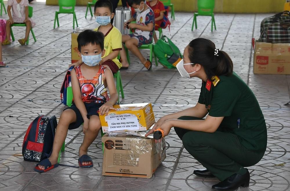 Nữ quân nhân cũng tham gia các khung cách ly, chăm có công dân diện F1. Trong ảnh: Một nữ quân nhân thuộc Ban CHQS TP Bắc Giang động viên các cháu bé trước khi hết hạn cách ly.