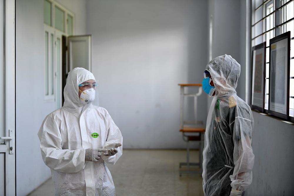 Nhân viên y tế trao đổi với cán bộ Ban CHQS huyện Việt Yên về công tác bảo đảm cách ly công dân.