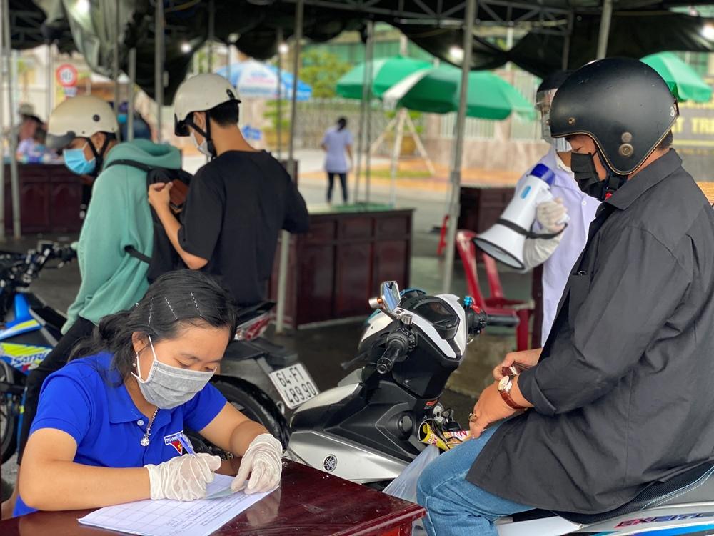 Các tình nguyện viên ghi nhận thông tin người dân khi qua các chốt kiểm soát xe máy ra vào cửa ngõ quận Cái Răng, TP Cần Thơ.