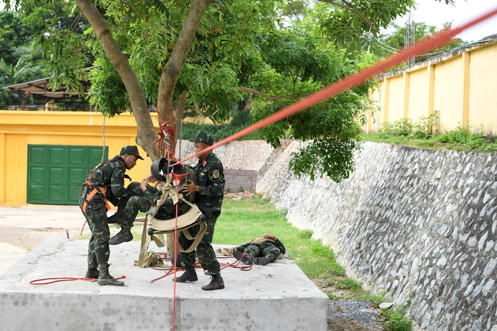 Các vận động viên tập luyện mắc dây ròng rọc vận chuyển thương binh qua sông.