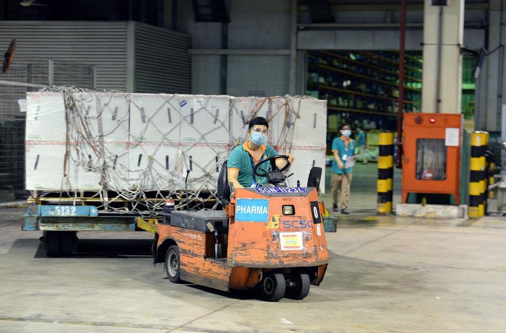 Chiếc xe rơ-moóc chuyên dụng cỡ nhỏ chở những kiện vaccine Moderna đầu tiên ra sảnh giao hàng của sân bay.