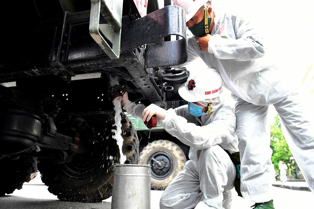 Các chiến sĩ chuẩn bị hóa chất đổ vào bồn xe.